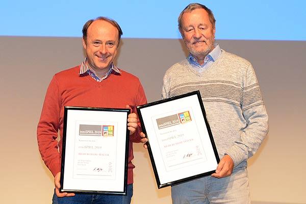 Walter Scholz von Zoch und Autor Jürgen Adams nehmen den INNO Spiel für Ab durch die Mauer entgegen