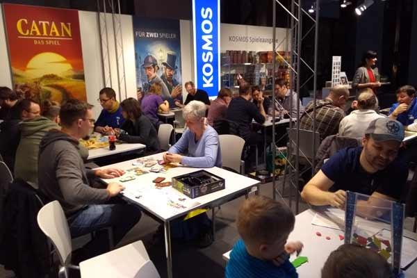 Spieler spielen eine Auswahl an Spielen am Stand von Kosmos - Foto von Dirk Janßen